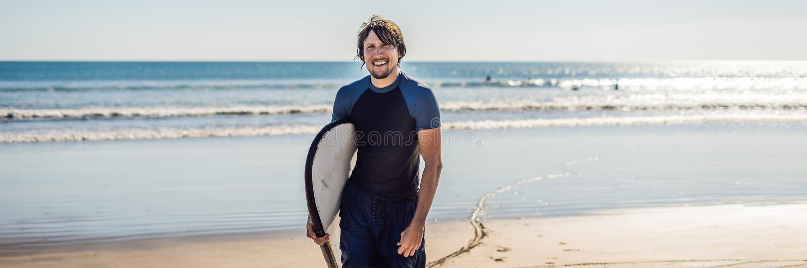 Handsome sporty young surfer posing with his surfboard under his arm in his wetsuit on a sandy tropical beach BANNER long format royalty free stock photography