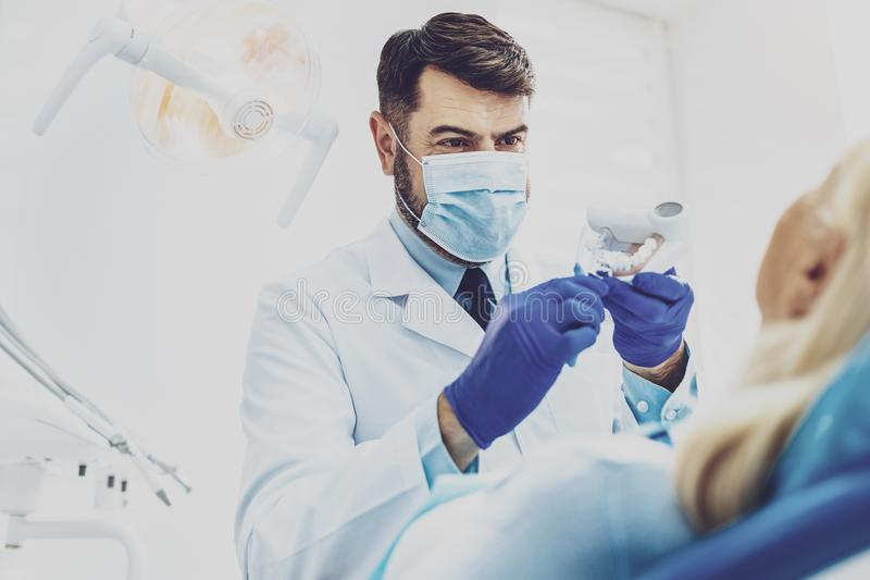 Handsome stomatologist demonstrating artificial jaw. So easy. Competent dentist raising hands while holding model of teeth royalty free stock images