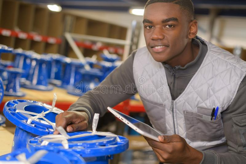 Handsome store manager with computer tablet in warehouse royalty free stock photography