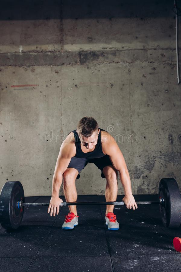 Handsome strong athlete is going to lift a barbell. On the gray background. hobby. interest royalty free stock image