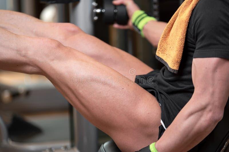 Handsome strong man performed leg press workout in the gym. Handsome strong man performed leg press workout in the gym stock images