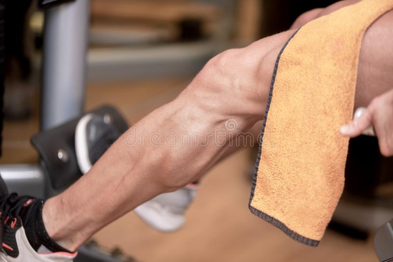 Handsome strong man performed leg press workout in the gym. Handsome strong man performed leg press workout in the gym stock photo