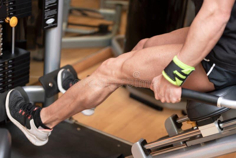 Handsome strong man performed leg press workout in the gym. Handsome strong man performed leg press workout in the gym royalty free stock photography