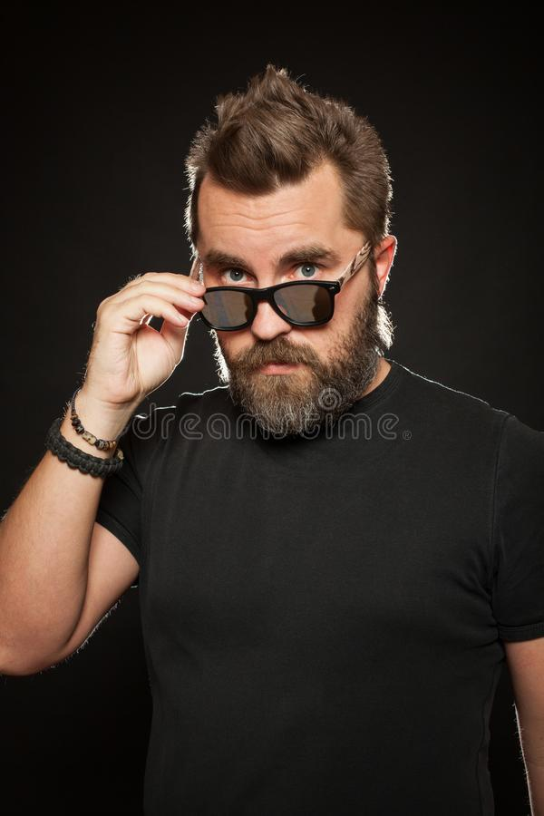 A handsome, strong man with a stylish hairstyle and beard dresses sunglasses in the Studio on a black background royalty free stock image