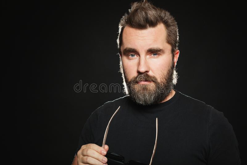 A handsome, strong man with a stylish hairstyle and beard dresses sunglasses in the Studio on a black background. With copy space royalty free stock photography