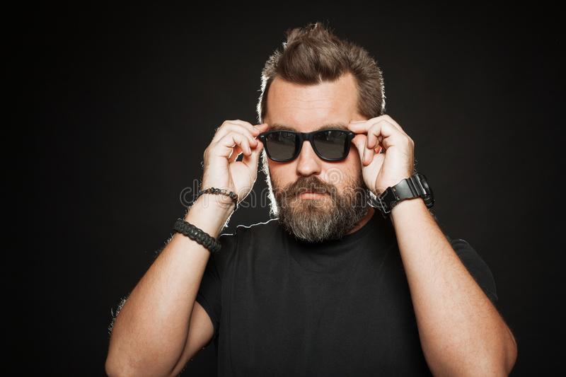 A handsome, strong man with a stylish hairstyle and beard dresses sunglasses in the Studio on a black background. With copy space royalty free stock images