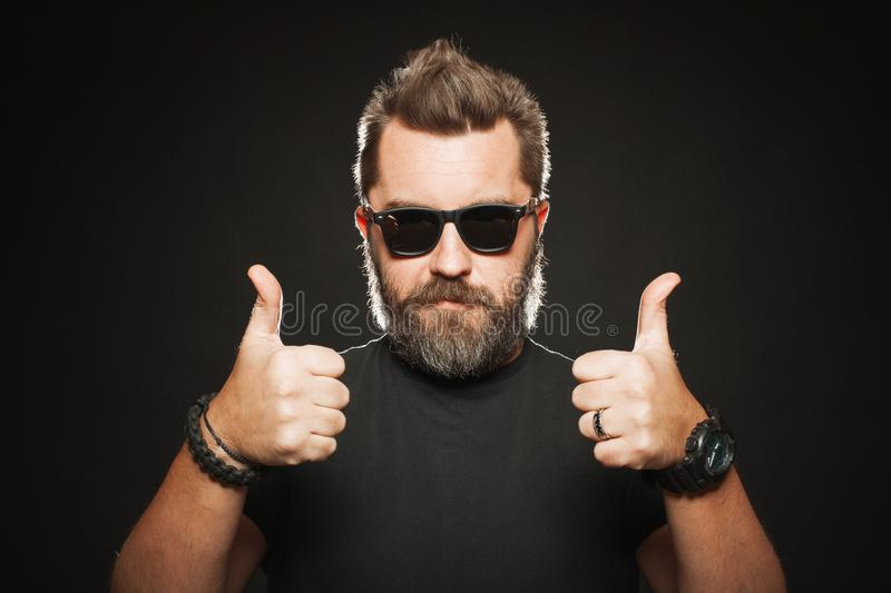 A handsome, strong man with a stylish hairstyle and beard shows two thumbs up in the Studio on a black background. With copy space stock images