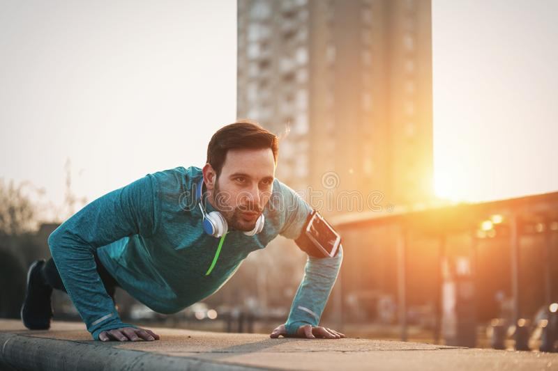 Handsome strong sporty male doing exercises outdoor. Handsome strong sporty male doing push up exercises outdoor royalty free stock photo