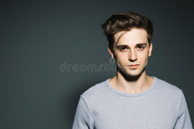 Handsome in style. Cheerful young man in smart casual wear while standing against grey background royalty free stock photo