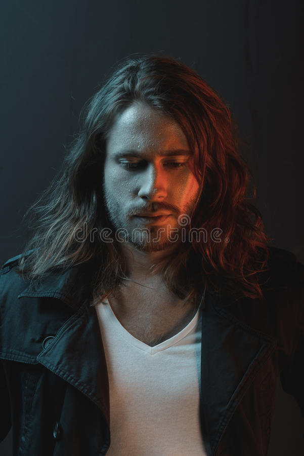 Handsome stylish bearded young man with long hair looking down in studio royalty free stock image
