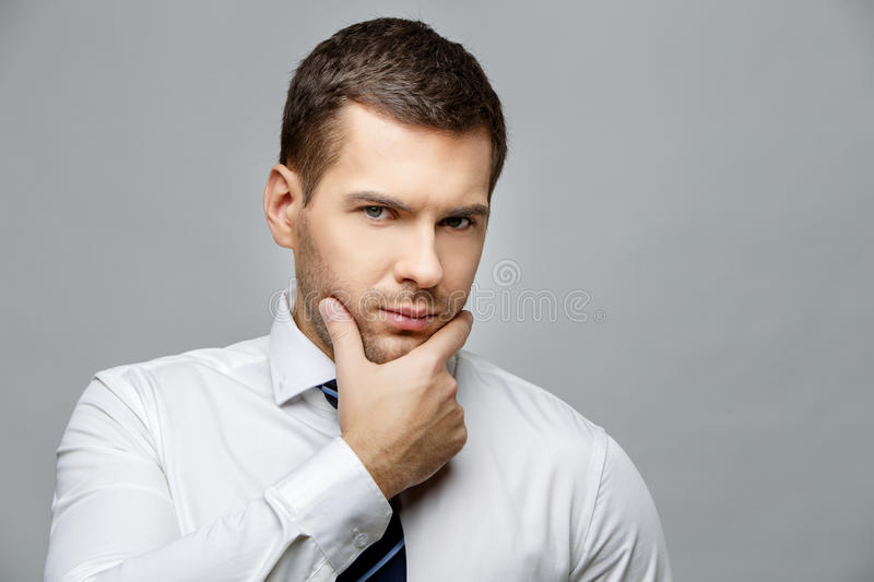Handsome stylish businessman on grey background. Handsome stylish caucasian businessman on grey background with copy space royalty free stock image