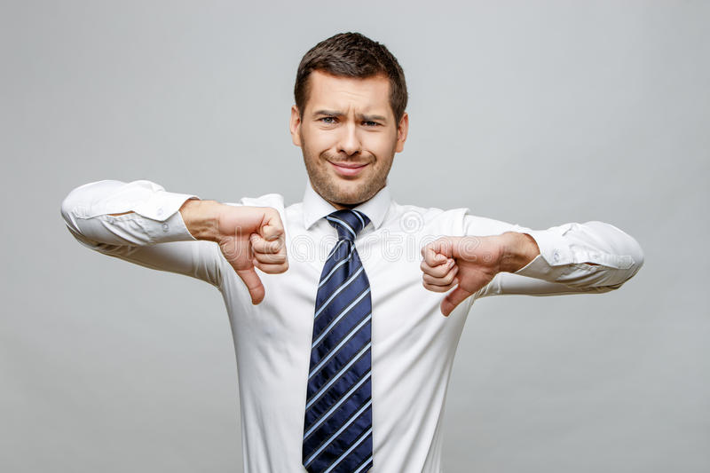 Handsome stylish businessman on grey background. Handsome stylish caucasian businessman on grey background with copy space royalty free stock photo