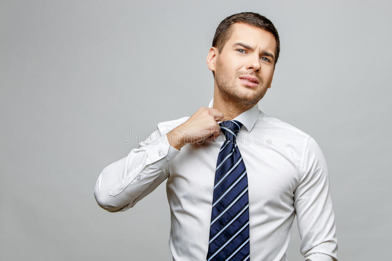 Handsome stylish businessman on grey background. Handsome stylish caucasian businessman on grey background with copy space royalty free stock images