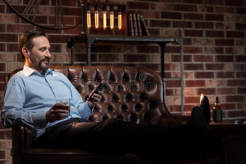 Handsome stylish businessman putting his legs on the table. Comfortable position. Happy content stylish man putting his legs on the table and looking at his royalty free stock image