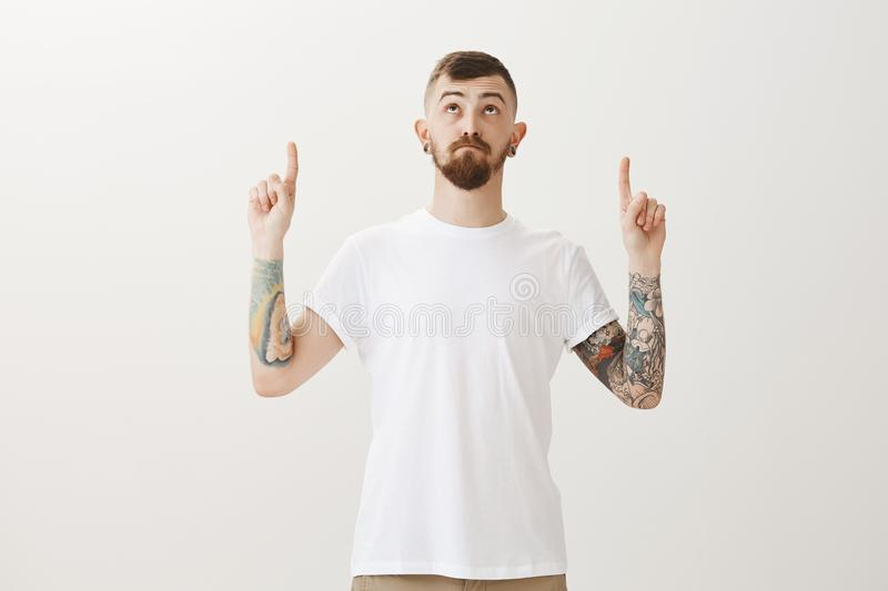 Handsome stylish caucasian urban guy with beard and tattoos, pointing and looking up with curious interested expression royalty free stock images
