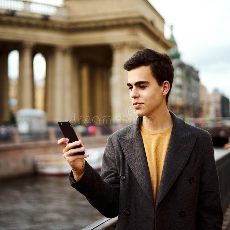 Handsome stylish fashionable man talking on phone, dialing chat message, brunette in elegant gray coat is standing on street in royalty free stock photo