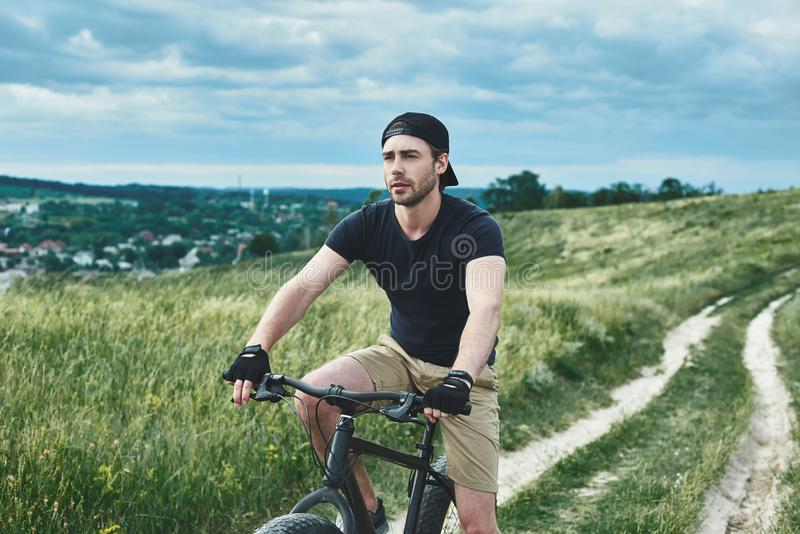 Handsome stylish guy cycling at the mountains royalty free stock photos