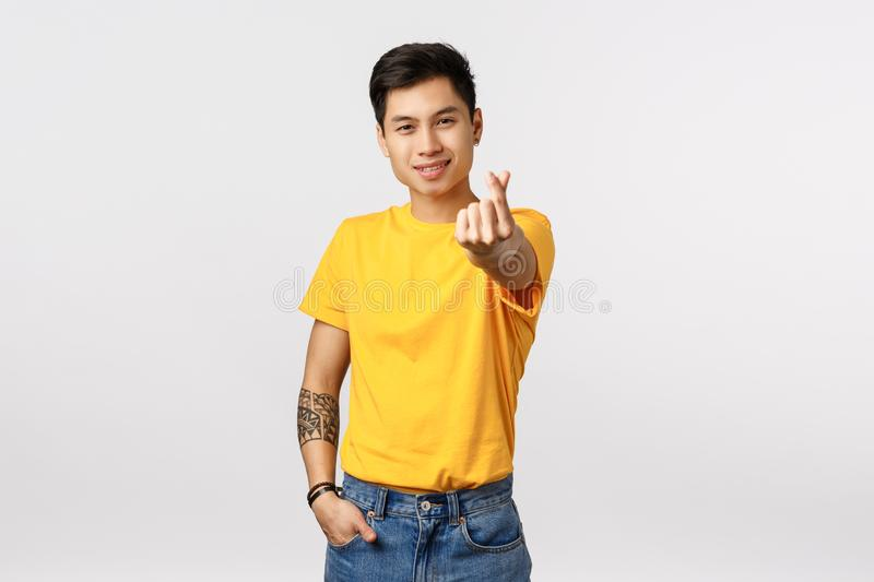 Handsome and stylish hipster asian guy in yellow t-shirt, with tattoos, extend arm and showing korean heart love sign. Smiling silly, express affection, adore stock image
