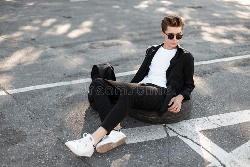 Handsome stylish hipster man relaxes sitting on the asphalt. Modern guy model in fashionable elegant black clothes. In dark sunglasses with a black trendy royalty free stock photos