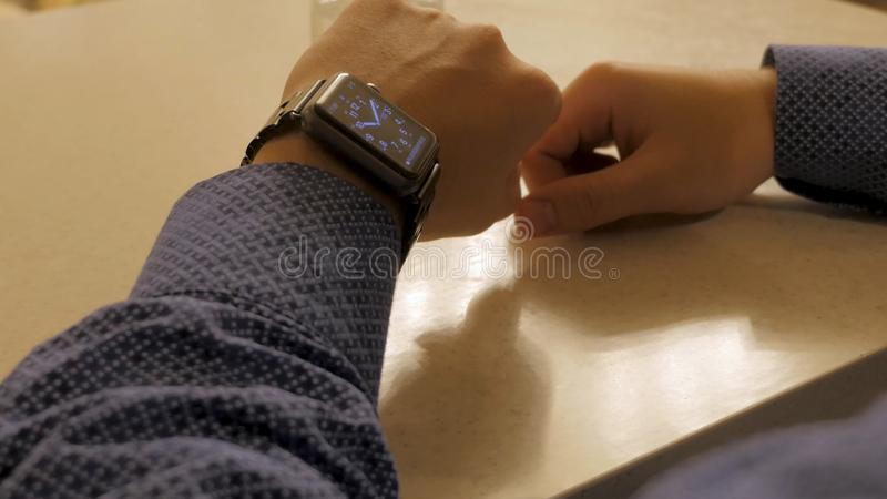 Handsome stylish male managing time on electronic watch. Young man checking modern wrist clock royalty free stock photo