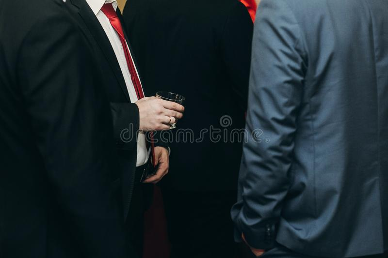 Handsome stylish man with alcohol drink posing at business dinner party, corporate suit man holding glass in hands at restaurant. Reception, wedding concept stock photography
