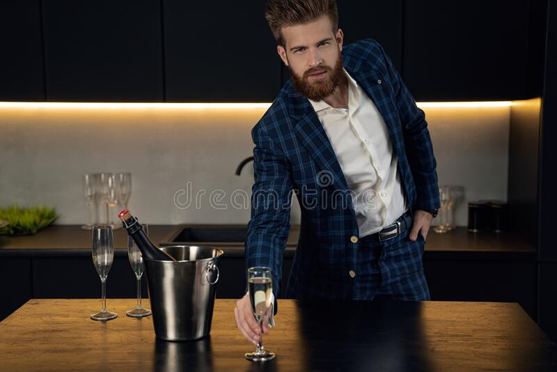 Handsome stylish man in blue suit in cage at home. Standing in modern black kitchen with glass of champagne stock images