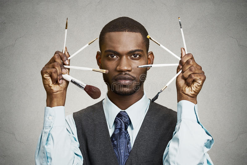 Handsome stylish man holding make-up brushes. Closeup portrait headshot handsome business man, corporate executive holding make-up brushes by his face black royalty free stock photography