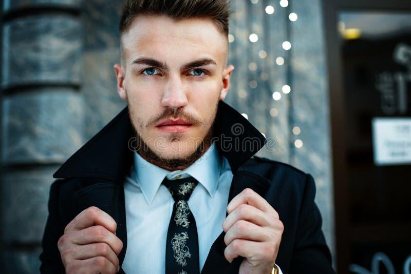 Handsome stylish man. Portrait of handsome stylish man in elegant black coat and white shirt outdoors stock photos