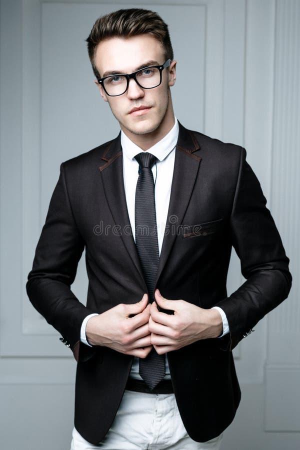 Handsome stylish man. Portrait of handsome stylish man in elegant black suit wearing eyeglasses royalty free stock photo