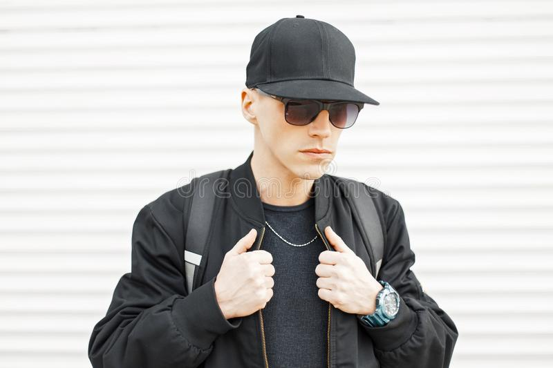 Handsome stylish man in sunglasses and a black baseball cap royalty free stock images