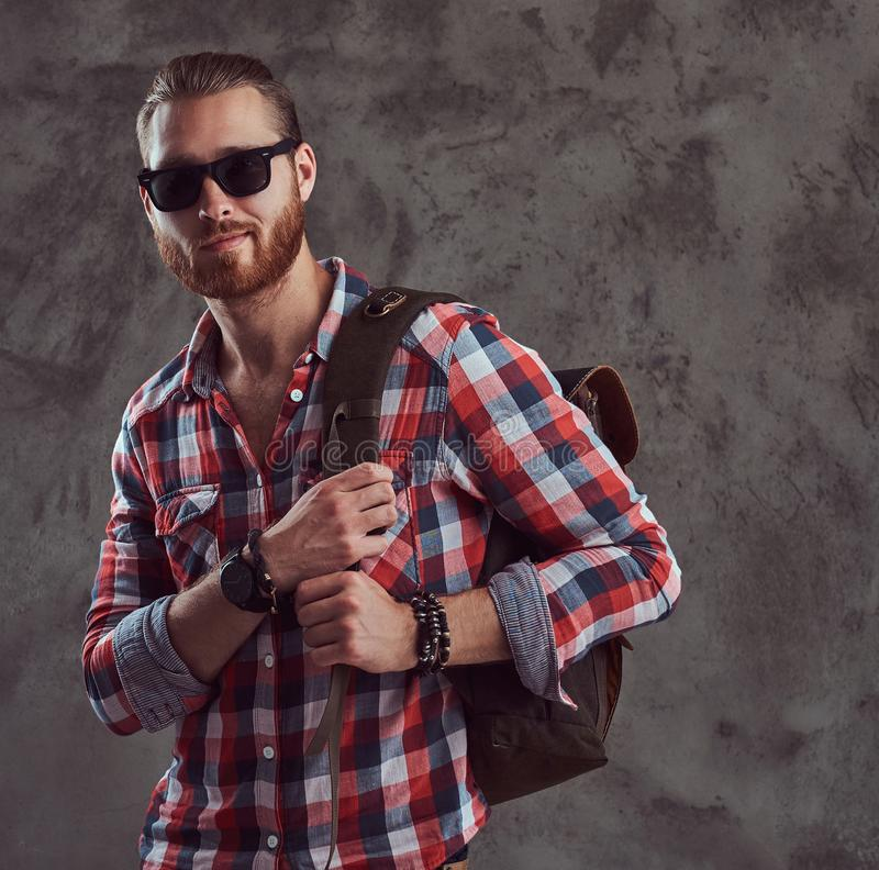 Handsome stylish redhead traveler in a flannel shirt and sunglasses with a backpack, posing in a studio on a gray royalty free stock image