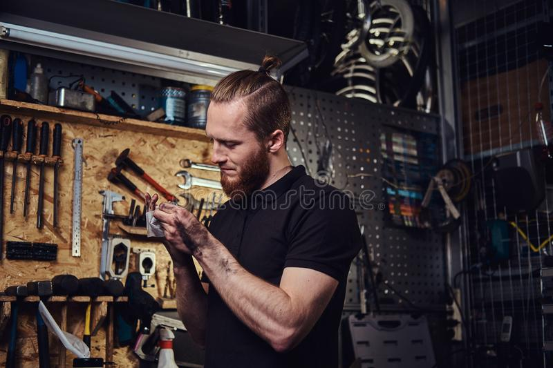 Handsome stylish redhead worker, cleaning his dirty hands after repairing working in a workshop. royalty free stock images