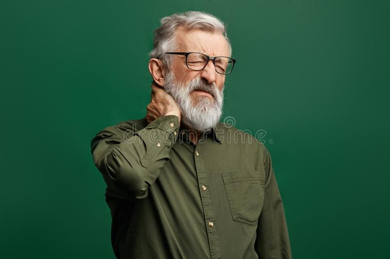 Handsome stylish senior man in green shirt suffers from neck ache stock photo