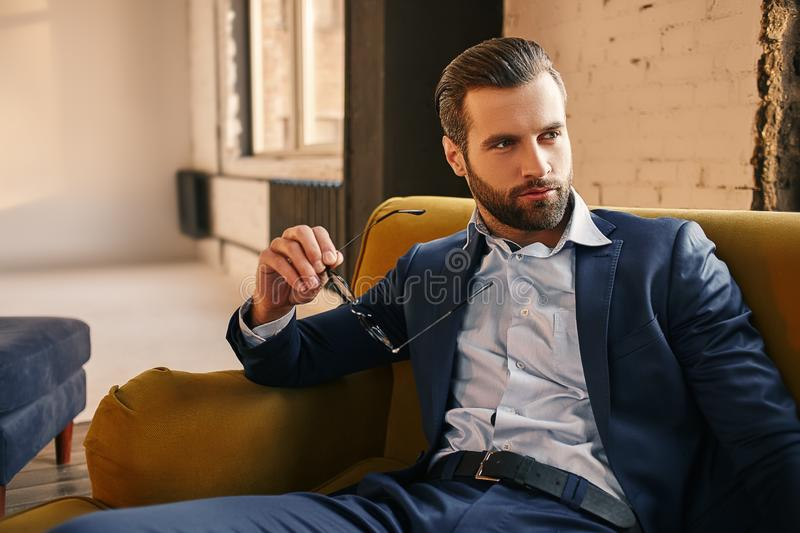 Handsome and stylish...Young businessman in fashion suit is holding glasses, sitting on sofa and thinking about stock photos