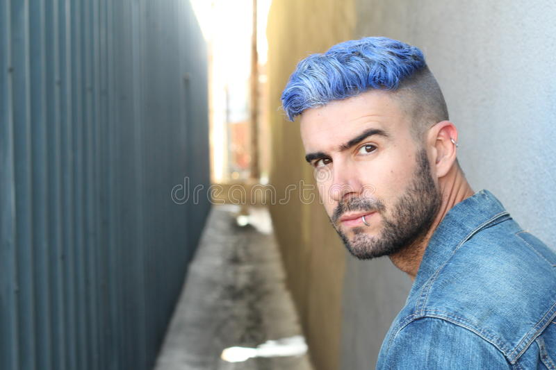Handsome stylish young man with artificially coloured blue dyed hair undercut hairstyle, beard and piercings with copy space stock photos