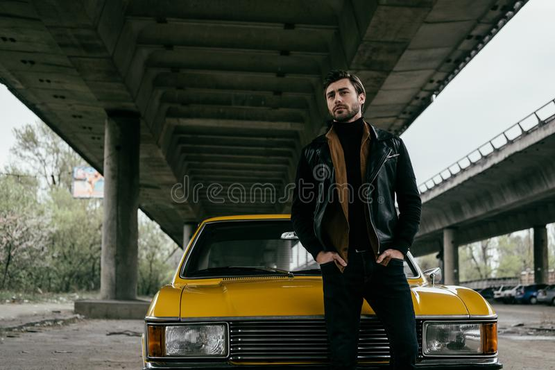 handsome stylish young man in leather jacket standing with hands in pockets near yellow royalty free stock images