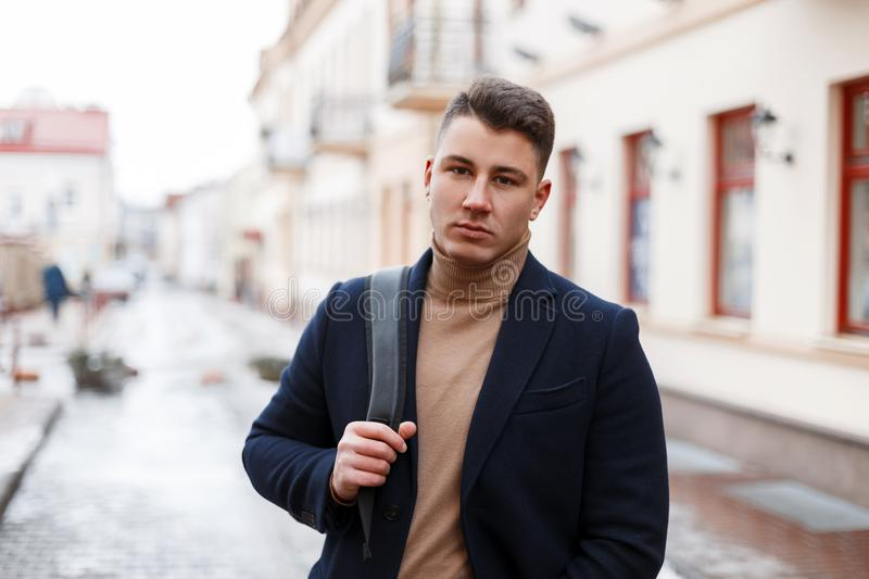 Handsome stylish young man in trendy clothes with a black stylish backpack walks through the city streets on a warm spring day. royalty free stock image