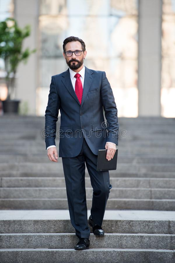 Handsome successful businessman descending city stairs. Full length of attractive middle aged businessman keeping digital tablet in hand while descending city stock photography