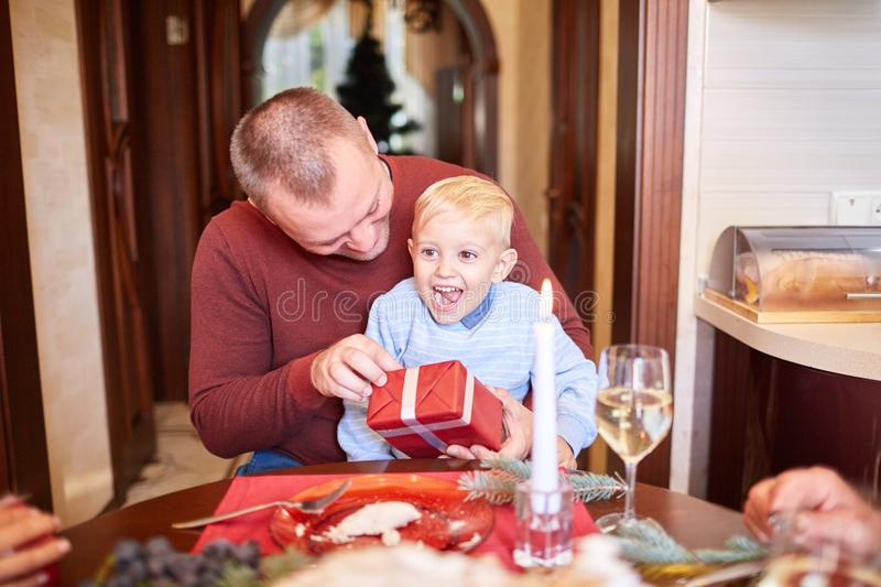 Dad giving a red gift to little son on a festive background. Family Christmas presents concept. Handsome and successful father giving a big red present box to stock photos