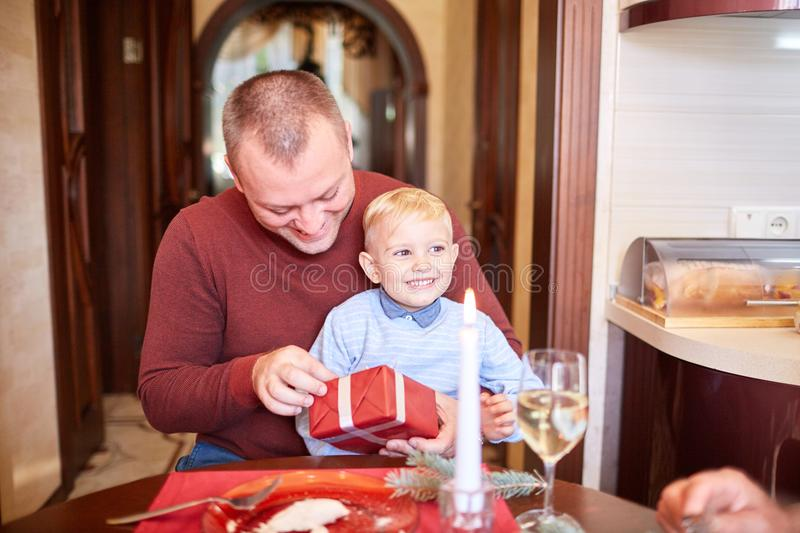 Dad giving a red gift to little son on a festive background. Family Christmas presents concept. Handsome and successful father giving a big red present box to stock photo