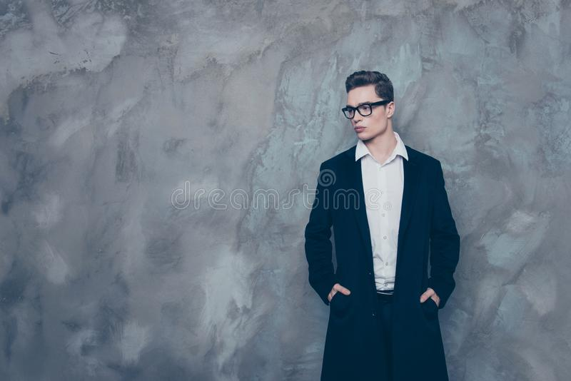Handsome successful young guy in spectacles and black coat stand royalty free stock photography