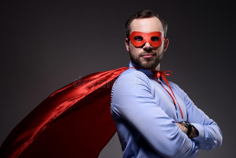 handsome super businessman in mask and cape with crossed arms looking at camera stock photo