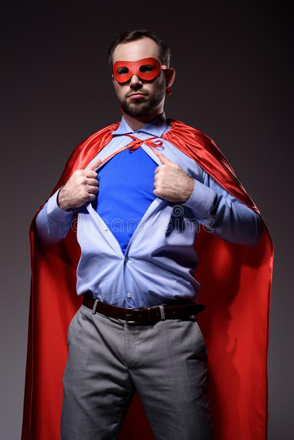 handsome super businessman in mask and cape showing blue shirt stock images