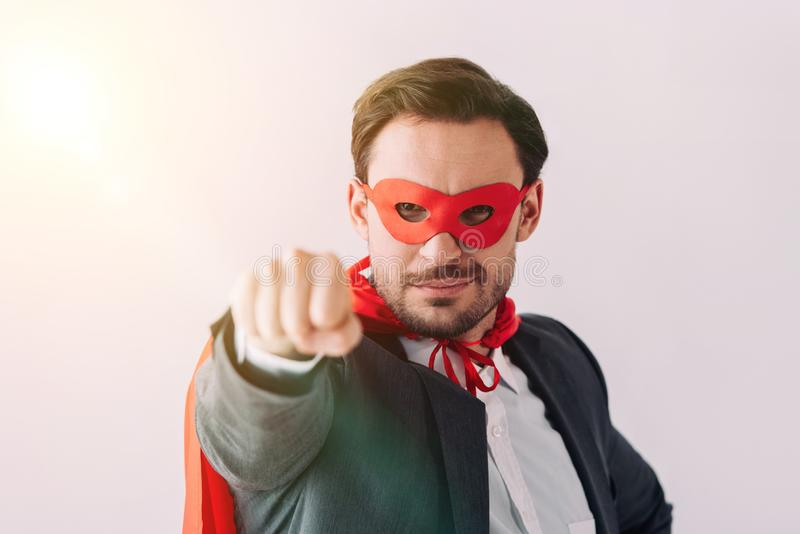 handsome super businessman in mask and cape showing fist stock photography