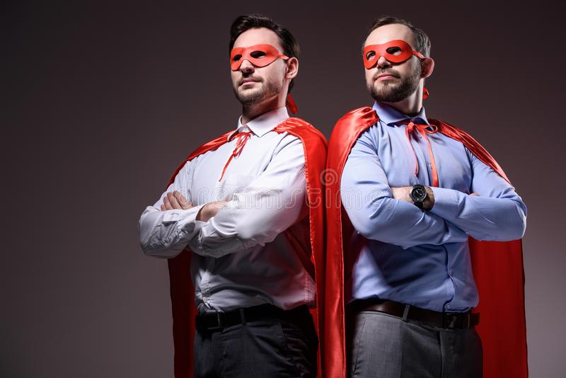handsome super businessmen in masks and capes standing with crossed arms stock photography