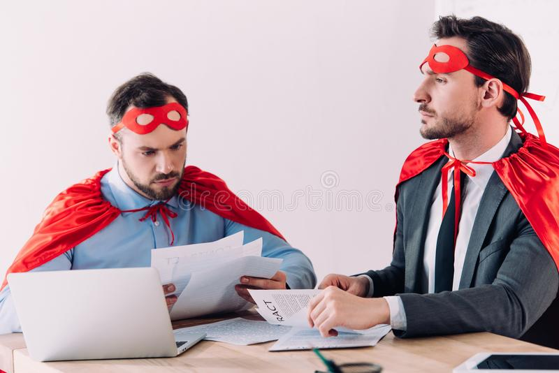 handsome super businessmen in masks and capes working with documents royalty free stock photography