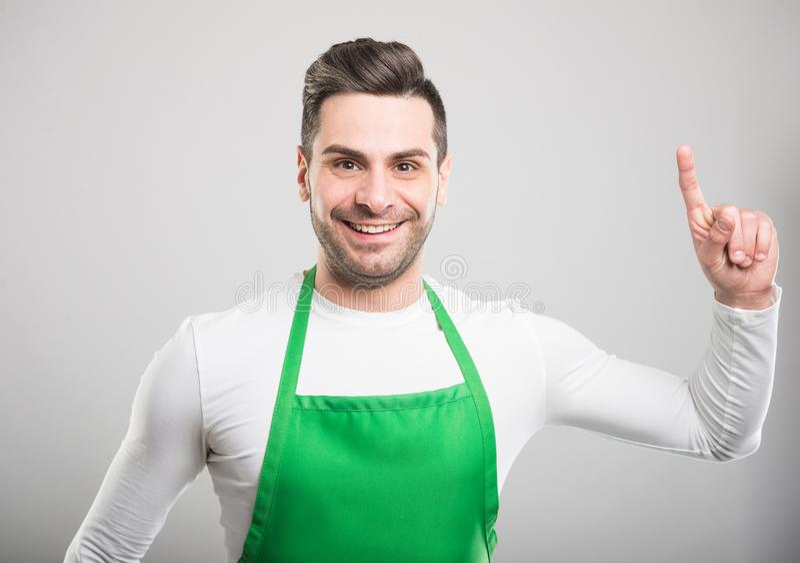 Handsome supermarket employer holding finger like good idea. And smiling on white background stock image
