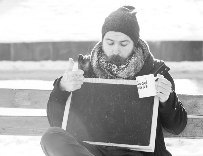 Handsome surprised man, hipster with beard and moustache covered with white frost, holds blank black board and cup with stock photo