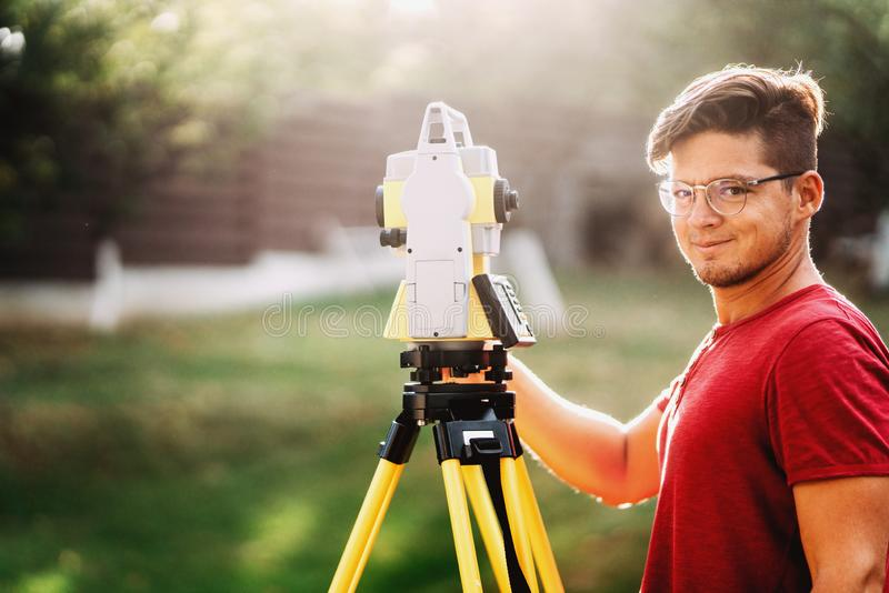 Handsome surveyor working with total station with coordinates, cartography industry details. Portrait of handsome surveyor working with total station with stock photos
