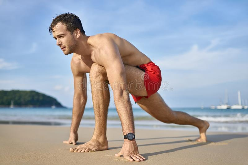 Tanned guy on beach. Handsome tanned man on the sand beach on the sunny background of the sea with white boats and the blue sky. He wears a red swim trunks and a royalty free stock photos
